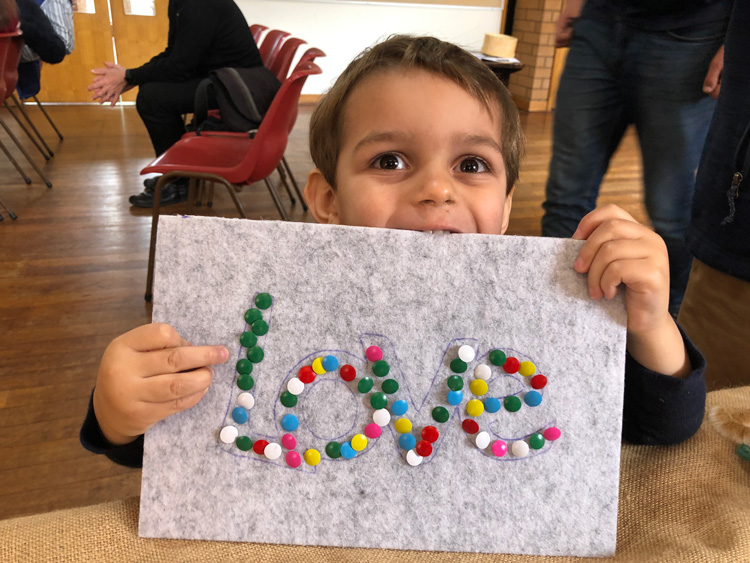 Child holding a craft paper with the word love.